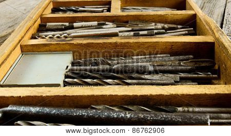 Drills in box on a wooden background.