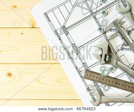Drawings for building and many metal working tools on wooden background.