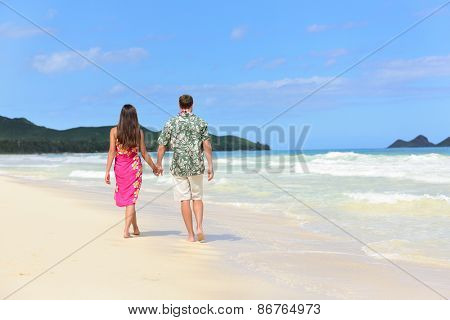 Hawaii honeymoon couple of newlyweds walking on tropical beach in Hawaiian apparel, pink sarong dress and green Aloha shirt for Polynesian cultural tradition. Young people holding hands happy in love.