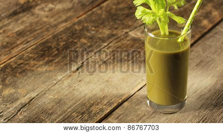 Glass with green juice, celery branch and straw.