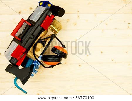 Tools in box on wooden background.
