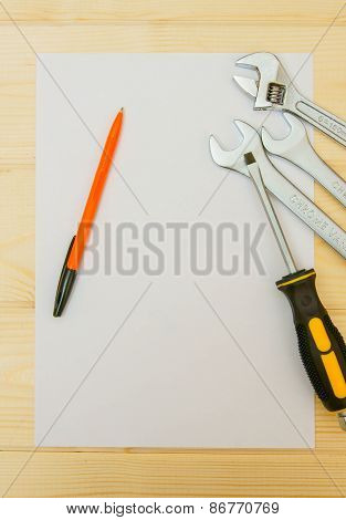 Paper with pencil and working tools on wooden background.