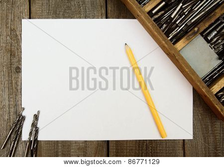 Paper with pencil and box, drills on wooden background.