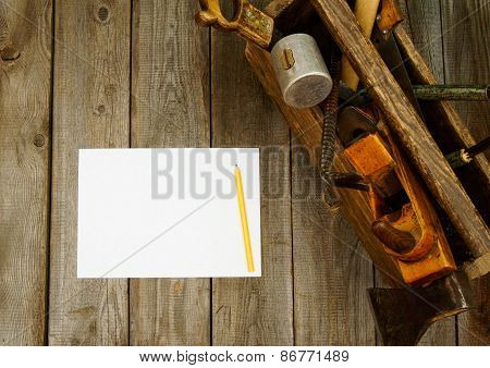 Paper with pencil and old tools in box on wooden background.
