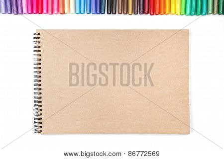 Row of colored felt tip pens with notebook