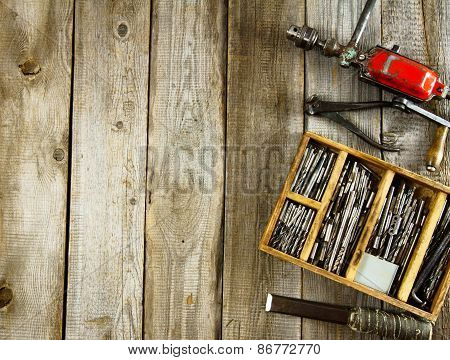 Drills in box, drill, chisel on a wooden background.