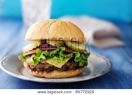 gourmet cheeseburger on colorful blue rustic table top