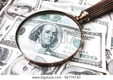 Dollars and magnifying glass