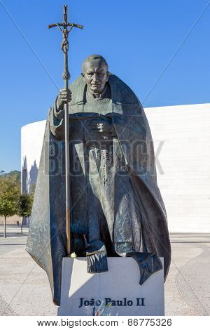 Sanctuary of Fatima, Portugal, March 07, 2015 - Statue of Pope John Paul II with the Basilica of Most Holy Trinity in background. Fatima is one of the most important pilgrimage locations for Catholics