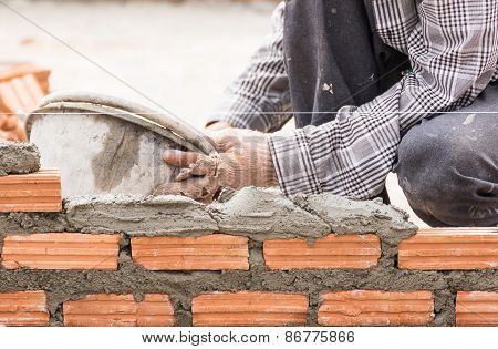 Bricklayer Working In Construction Site Of A Brick Wall