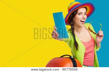 Woman tourist with travel suitcase and blue boarding pass, isolated on summer background