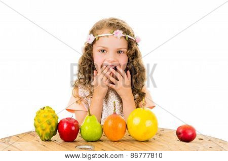 Cute little preschooler girl with fruits on the table