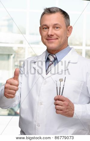 Dentist with tools showing thumb up