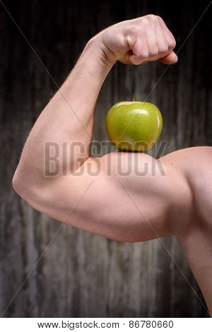 Close up of sporty man demonstrating biceps with apple