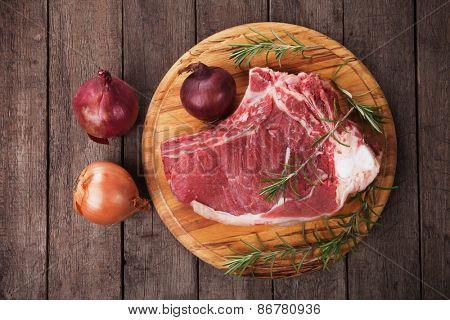 Raw ribeye beef steak on wooden board, overhead shot