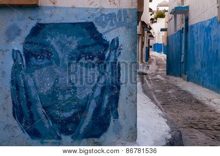RABAT, MOROCCO - MAR 8 2015 : A pensive gaffiti face stares down the street in the Kasbah.