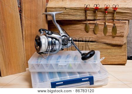 Fishing Reel With Metal Baits On Wooden Background.