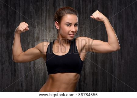 Smiling mixed race sporty woman demonstrating her biceps