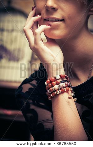 young woman portrait with lot of bracelets on hand, fashion detail, indoor shot