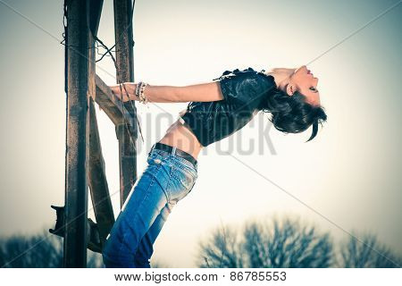 young rebel woman in blue jeans and leather jacket outdoor shot on old metal construction hot sunny day