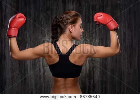 Back view of mixed race sporty woman with boxing gloves