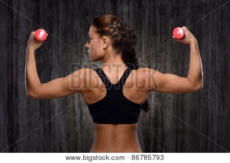 Back view of mixed race sporty woman with dumbbells