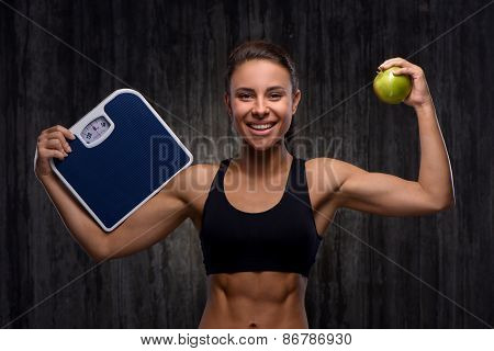 Smiling mixed race sporty woman holding weighs and apple