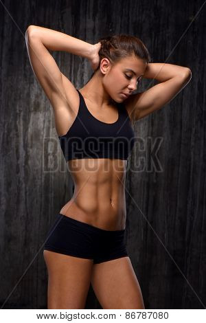 Mixed race sporty woman demonstrating biceps and slim figure
