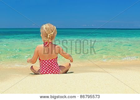 Little Girl Relaxing On The Sand Beach Edge