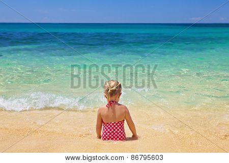 Girl Sitting On The Sand Beach