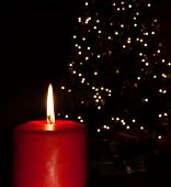 stock photo of candle flame  - Candle with a flame brighter than the Christmas tree behind - JPG