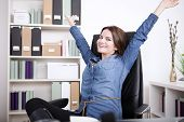 pic of extend  - Happy Office Woman in Denim Blouse Sitting on her Office Chair While Extending her Arms and Looking at the Camera - JPG