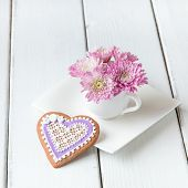 foto of mums  - Cup full of pink mum flowers and heart shape cookie on white wooden table - JPG