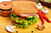 image of pepper  - Tasty hamburger filled with ham mushrooms cucumber and fresh salad garlic pepper pot and chili pepper on cutting board - JPG