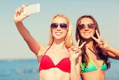 foto of two women taking cell phone  - summer vacation - JPG