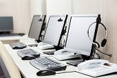 picture of telemarketing  - Row of computers with headphones on desk at call center - JPG