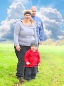 picture of child obesity  - Overweight parents with her son  playing together on spring meadows - JPG