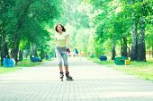 foto of roller-skating  - Roller skating sporty girl in park rollerblading on inline skates - JPG