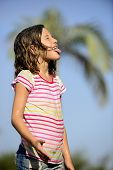 stock photo of dancing rain  - Happy smiling little girl outdoor in a sunny day enjoying the light rain - JPG