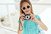 image of preteen  - Preteen child resting and taking photos at the beach in summer - JPG