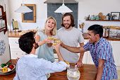 stock photo of racial diversity  - group of diverse friends having fun with drinks in kitchen - JPG