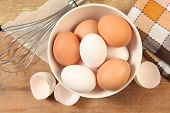 image of chicken-wire  - Eggs and whisk on wooden table - JPG