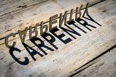 picture of carpentry  - wooden letters on old aged wooden table build the shadow word carpentry vintage style - JPG