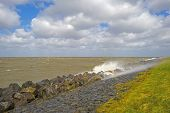 picture of dike  - Storm raging over a lake along a dike in spring - JPG