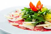 stock photo of rocket salad  - Isolated beef carpaccio served with salad rocket - JPG