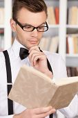 pic of bow tie hair  - Confident young man in shirt and bow tie reading a book and holding hand on chin while standing in library - JPG
