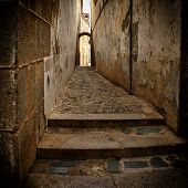 stock photo of cobblestone  - Detail of narrow cobblestone alley in Caceres (Spain)
