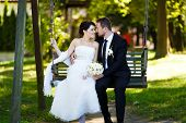 image of swing  - Bride and groom embracing on a swing on their wedding day - JPG