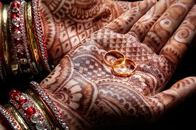 stock photo of hand god  - Woman hands with henna holding two golden wedding rings on black background - JPG