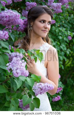 Beautiful Bride Posing Near Blooming Lilac Tree